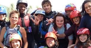 A group of young people in wetsuits
